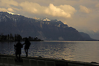 Couple walking along a wall on the shore of the lake Léman, Vevay close to Montreux,Lausanne Switzerland.