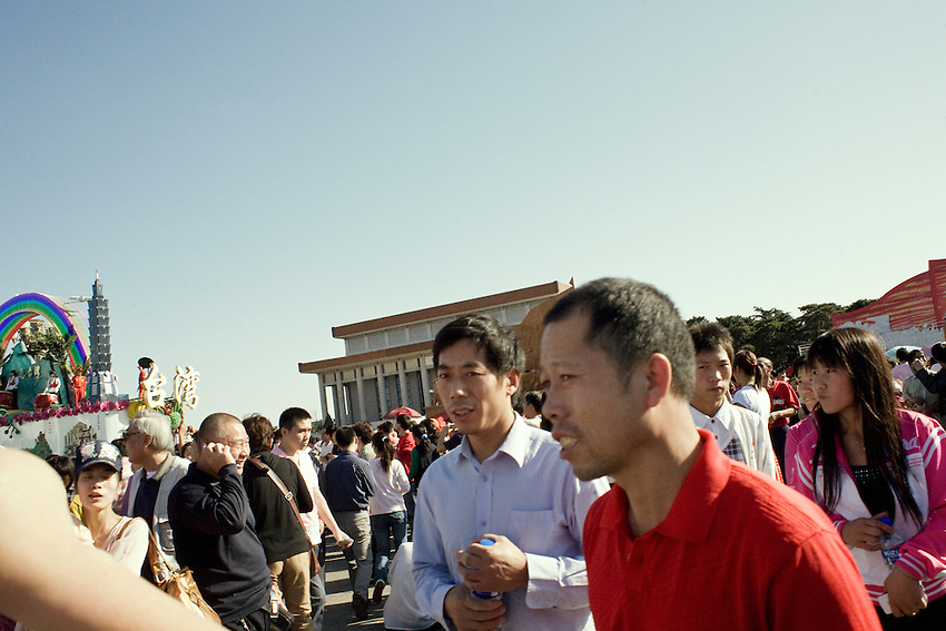 Four days after the celebrations of the 60th anniversary of RPC, beijingers are allowed to go to the Tiananmen square to see the parade vehicles. Here some mens take pictures near the Taiwan's parade vehicle... Taiwans is considered being a part of China in the government propaganda. In the background , the Mao's mausoleum.