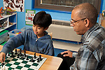 Afterschool chess program for elementary students graduates of Headstart program male teacher working with boy