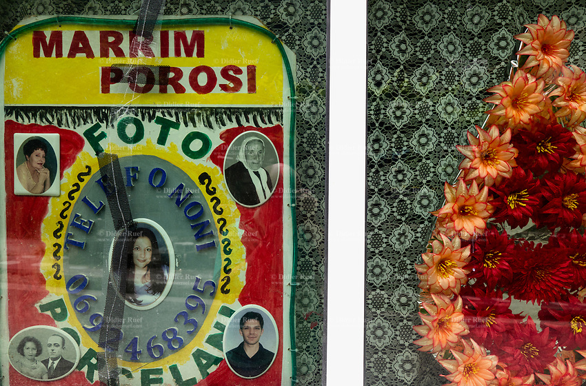 Albania. Gjirokastër. Town center. The shop window of a photo studio with various portraits of women, men and a couple. The photos are from young, mature and old persons. A plastic flower wreath and a curtain. The buildings is dating from the communist time. Gjirokastër is a city in southern Albania. 23.05.2018 © 2018 Didier Ruef
