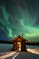 Man views the aurora borealis from Lee's Cabin in the White Mountains National Recreation Area