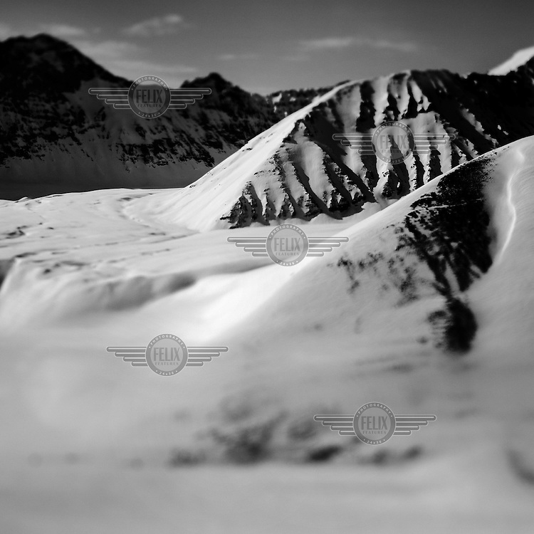 A snow covered mountain in East Greenland, north of Mestersvig. Mestersvig is a military outpost with a runaway in the Scoresby Land region of the Northeast Greenland National Park. Originally built in anticipation of mining in the area it has been run by the Danish defence department since 1988. The place is staffed by two men whose duties include maintenance of buildings and the airfield and support of other activities in the area.