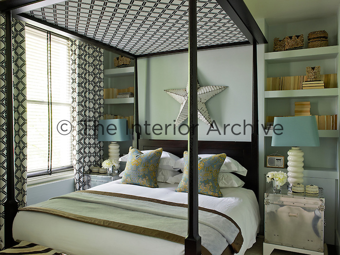 In the master bedroom matching stainless steel bedside tables flank the bed in front of bookshelves situated in alcoves behind