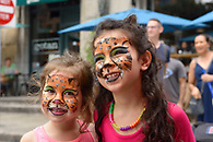 Two smiling sisters showing off their face painting.