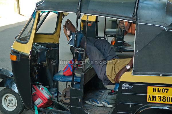 India, Kerala, Fort Cochin (Cochi, Kochi). Driver relaxing in his autorikshaw.