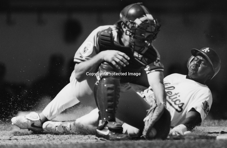 Oakland Athletics Jerry Brown slides safe, Kansas City catcher Brent Mayne tags.(1993 photo by Ron Riesterer)