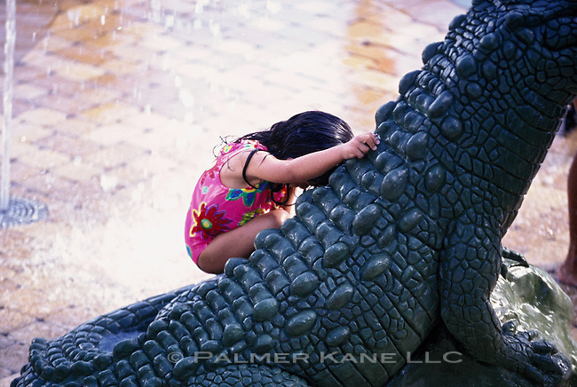 Girl Playing On Alligator Statue In Water Fountain