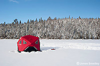 Ice fishing tent on a frozen lake in winter.