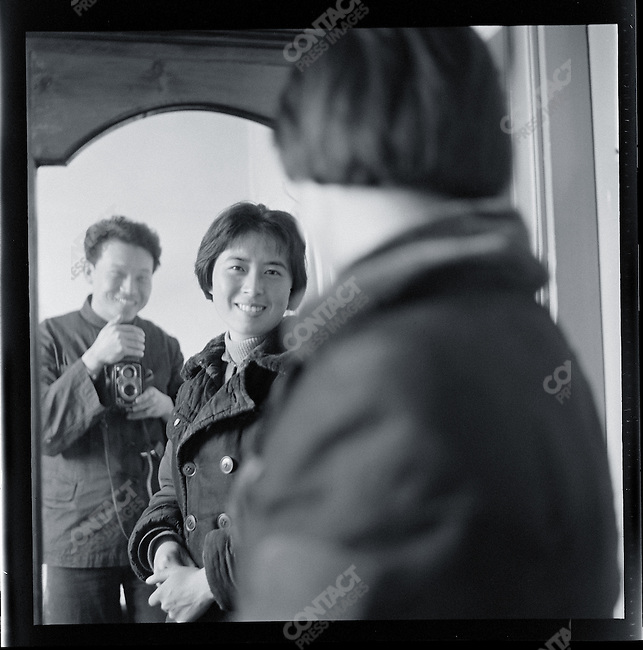 """Li Zhensheng photographs his girlfriend Sun Peikui in her apartment in Siping, Jilin province. Peikui lost her position as a schoolteacher after her mother, criticized as """"belonging to a landlord family,"""" committed suicide. 2 May 1967"""