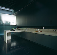 This kitchen has a concrete work surface which extends the length of the room and Roksanda Ilincic's work room is illuminated beyond