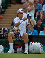 01-07-13, England, London,  AELTC, Wimbledon, Tennis, Wimbledon 2013, Day seven, Tommy Haas (GER)tapes his racketgrip<br /> <br /> <br /> <br /> Photo: Henk Koster