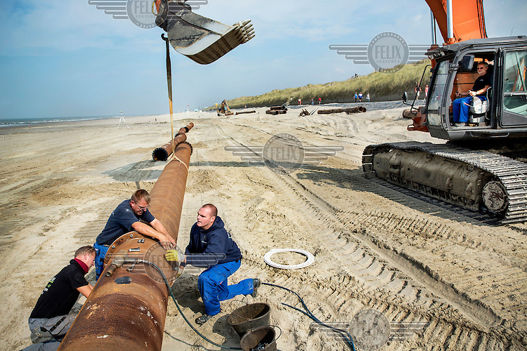 Workers construct a pipline as part of the Belgian Coast Safety Plan. The Governement launched this plan in order to protect the coastline against the threat of a super storm which could cause a major flood. This beach in Oostende will be covered with 500,000 m³ of sand in order to elevate it by one to three meters. The sand comes from a sand bank in the sea.
