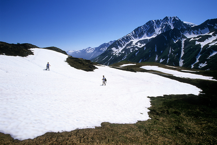 Hikers cross a melting field of snow on the Lost Lake Trail north of Seward, Alaska, in early June. The route winds through the Kenai Mountains in Chugach National Forest. Spring comes late in higher elevations, giving fans of winter an opportunity to enjoy two seasons at once.