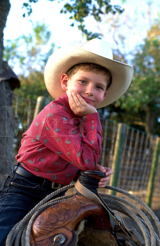 Portrait of a smiling young boy wearing a cowboy hat and western style shirt as he sits on a saddle.