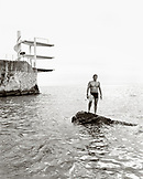 FRANCE, swimmer standing on rock in the Mediterranean Sea, Nice