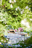 Glimpsed through the rose bushes a garden table with a bowl of freshly picked roses and pretty wrought-iron furnitre makes a romantic scene