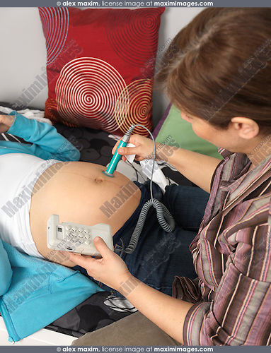 Midwife listening to a pregnant woman's baby heartbeat with a doppler fetal monitor