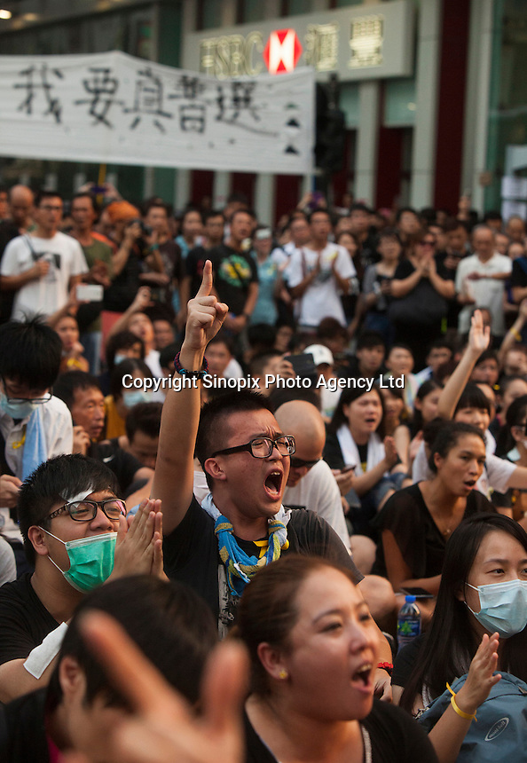 Pro-democracy protestoers cheer in the middle of an interesction controlled by activists in Mong Kok, on the second day of the mass civil disobedience campaign Occupy Hong Kong, Mong Kok, Kowloon, Hong Kong, China, 30 September 2014. The movement is also being dubbed the 'umbrella revolution' after the versatile umbrellas used to shield protesters from rain, sun - and police pepper spray.