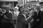 Smiling crowds line the street to watch the Pit Banners being parade through the town of Durham. With cigarette in hand, a gap and rotten toothed coal miner dances to the sound of a colliery silver bands, at the traditional annual Durham Miners Gala. County Durham, England 1974
