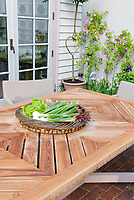 Garden patio table with vegetables, house door, roses Rosa climbing privacy wall, topiary, irises in spring flower, plants in containers on brick patio, elegant and simple small garden, pink and green color theme