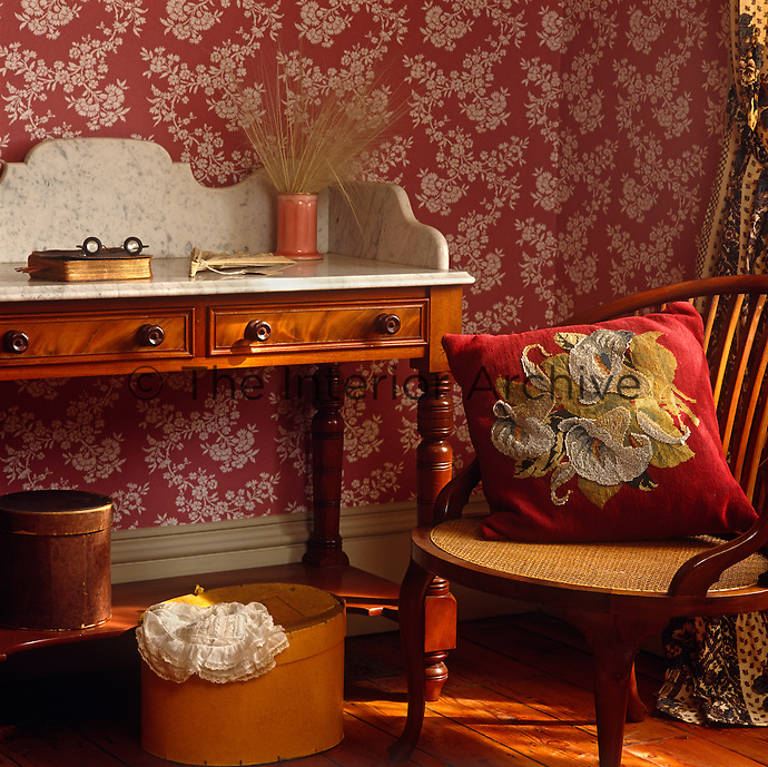 Corner of a wallpapered room with a marble-topped wooden washstand and an armchair with a cane seat