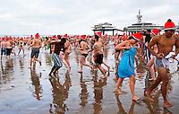 Traditionele Nieuwjaarsduik in Scheveningen. Mensen rennen de zee in