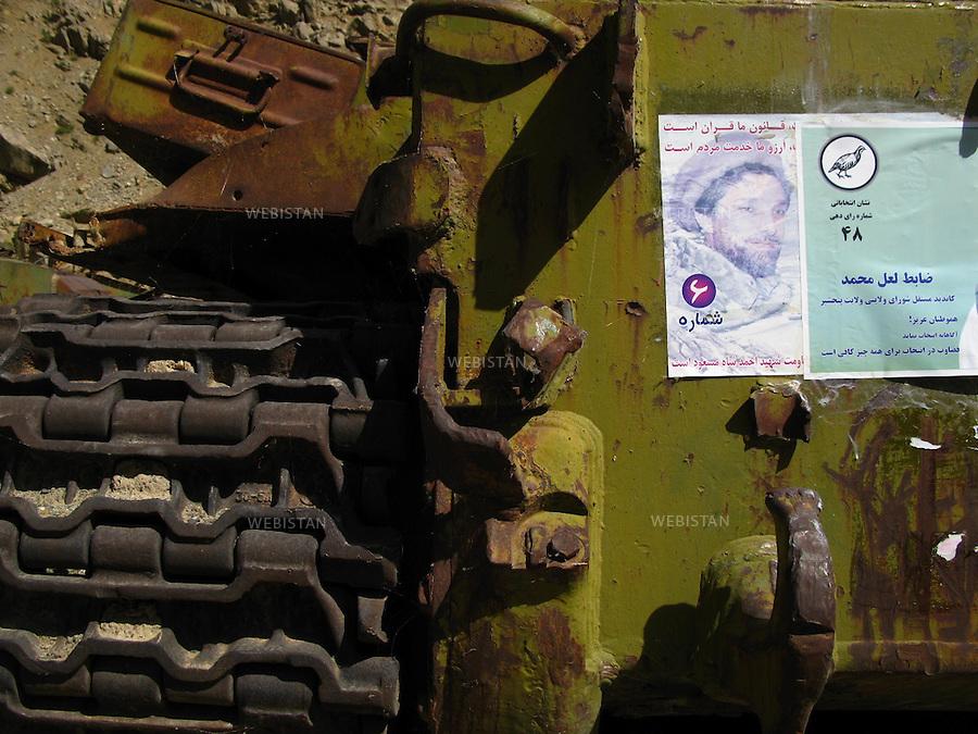 """AFGHANISTAN - VALLEE DU PANJSHIR - 18 aout 2009 : .Riviere du Panjshir. Passage de Dalan-Sangui, """"la gorge des rochers"""", ou eurent lieux des combats entre les troupes russes et celles du Commandant Massoud, lors de la guerre d'Afghanistan de 1979 - 1989. .Detail d'une carcasse de char pris aux russes par les Moudjahidin du Commandant Massoud lors de leurs assauts sur laquelle sont collees des affiches de campagne electorale..La photographie appartient a la serie """"Il etait une fois l'Empire Russe"""". ..AFGHANISTAN - PANJSHIR VALLEY - August 18th, 2009 : Panjshir River. The Dalan-Sangui Pass or """"Rocky Gorge,"""" where, during the Afghan war of1979-1989, many battles took place between Russian troops and those of Commander Massoud..Detail of an old Russian tank seized by Commander Massoud's mujahideen covered with campaign posters from the elections..The photograph is part of the series """"Once Upon a Time, the Russian Empire."""""""