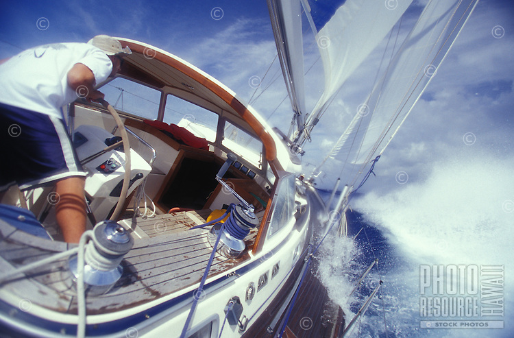 """Man at the helm of sailing yacht """"""""Heron"""""""", water washing over deck in rough ocean, off Oahu, Hawaii"""