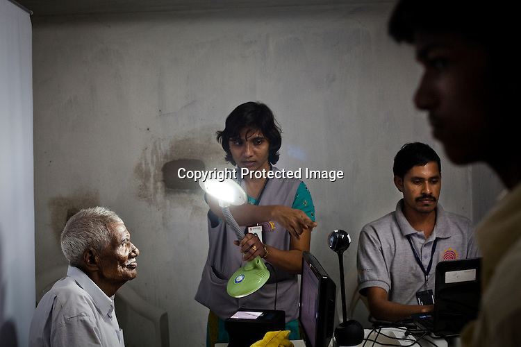 An official directs 95 year old Gandaiah to look at the camera to have his picture taken as part of the enrollment that is on its way in Naagaaram village, outskirts of Hyderabad in Andhra Pradesh, India. India is assigning each one of its 1.2 billion people a unique ID number based on digital finger prints and iris scan. Photograph: Sanjit Das/Panos