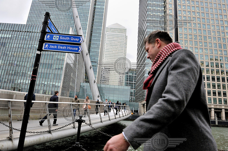A man, walking beneath the skyscrapers of Canary Wharf in London's Docklands. Behind him people are crossing the City Canal via the South Quay Footbridge.