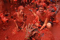 BUNYOL, SPAIN - AUGUST 31: People immersed in tomato juice during the Tomatina August 31, 2005 in Bunyol, Valencia, Spain. Approximately 45,000 people pelted each other with a little over 100.000 kilograms of tomatoes. The tomatina is known as the world's largest tomato battle. Photo by Ander Gillenea