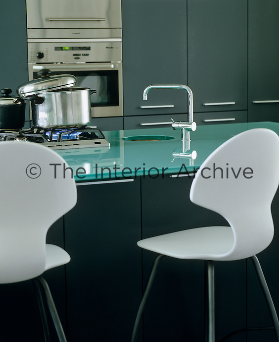The kitchen island which doubles as an informal dining area has a glass work surface