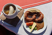 Brotzeit mit Brezel  und Weißwurst im Allgäu, Bayern, Deutschland<br /> Light meal with pretzel and bavarian sausage, Allgäu, Bavaria, Germany