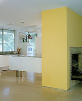 In an open-plan Florida house the fireplace wall painted a bright primrose yellow divides the kitchen from the living area