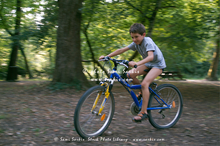 Boy having fun riding alone on his bike in a forest, Canejan, Gironde, France.