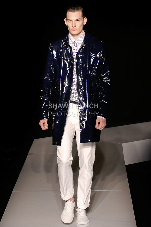 Bryce walks runway in a navy blue patent leather rain coat, white and blue cotton striped jersey sport shirt, white cotton 5 pocket pant, royal blue and ivory silk reversible knit tie, and navy leather belt, from the Joseph Abboud Spring Summer 2013 fashion show, during New York Fashion Week Spring 2013.