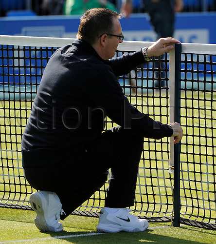 07.06.2011 The AEGON Championships from Queens Club in London. A linesman measures the height of the net on day two of the Aegon Championships at the Queen's Club.