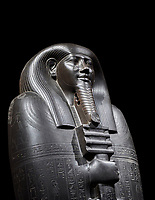 Ancient Egyptian greywacke sarcophagus lid of Ibi - late Period, 26th Dynasty (664-610BC). Egyptian Museum, Turin. black background<br /> <br /> Ibi was overseer of the priests of Thebes and chief steward of Nitocris, Divine Adoratrice of Amon during the reign of Psamtek I. The sarcophagus lid shows his hands emerging from a shroud to grasp the dfed-pillar, which allows him to rise to his feet again after resurrection. The lid weighs more than a ton and is finely sculpted. Despite the hardness of the greywacke stone the sarcophagus is made from, its makers have shown incredible skill creating a sarcophagus with intricate detail and a highly polished finish.