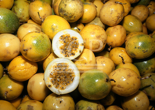 Brazil. Pile of Passion Fruit (Passiflora sp.) (maracaju) with one cut open to show the seeds and pulp.