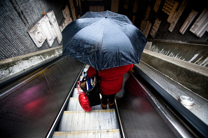 """Sylvia Romero descends with her Valentine's Day balloons into the 24th and Mission BART station in San Francisco, Calif., Friday Febuary 14, 2011. """"It's too wet.  I just hope my husband has something planned indoors"""" Romero said.  (Photo by Bryce Yukio Adolphson, © 2011)"""