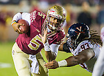 Florida State quarterback Jameis Winston scrambles to avoid Virginia defensive tackle Donte Wilkins when Florida State defeated Virginia 34-20 in an NCAA football game in Tallahassee, FL November 8, 2014