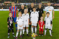 Children mascots with Scott Dann of Crystal Palace (L) match official and referee Craig Pawson and Federico Fernandez of Swansea City ]\during the Premier League match between Swansea City and Crystal Palace at The Liberty Stadium, Swansea, Wales, UK. Saturday 23 December 2017