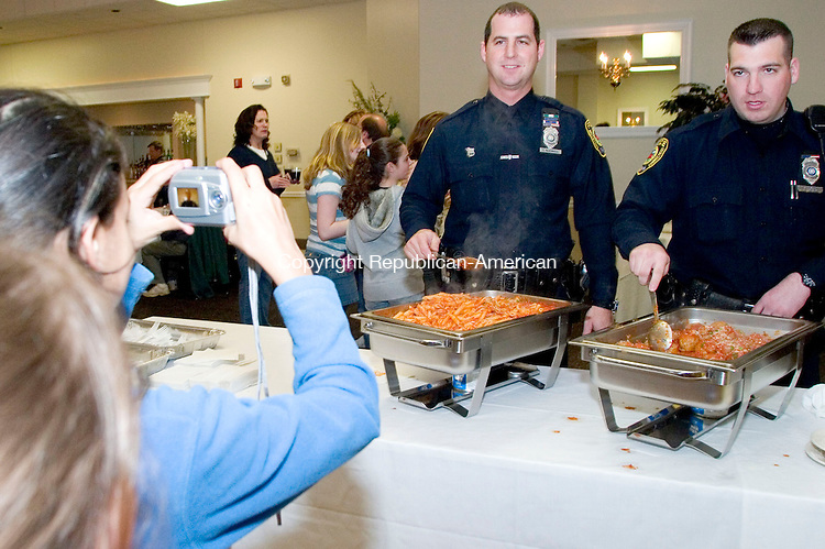 WATERTOWN, CT- 12 APRIL 07- 041207JT05- <br /> At left, Marilyn Howieson, with Alexa Giammattei behind her, takes a picture of Watertown Police Officers Tom McDonnell, left, and Mark Conway during the annual fundraising dinner of the Water-Oak CrimeStoppers at the Grand Oak Villa in Watertown on Thursday. The recipient for the CrimeStopper of the Year Award was Dr. Joseph Erardi, Superintendent of Schools for Watertown.<br /> Josalee Thrift Republican-American