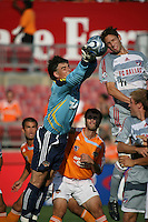 Houston Dynamo goalkeeper Pat Onstad (18) punches the ball away as FC Dallas defender Clarence Goodson (11) attempts the header.  Houston Dynamo defeated FC Dallas 1-0 in an MLS regular season match at Robertson Stadium in Houston, TX on August 19, 2007.