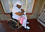 Jennifer Mhlanga suffered a spinal injury in a bus accident, and today uses a wheelchair to get around Harare, Zimbabwe. Here she sits on the porch of her house with her three-year old granddaughter, Tariro Bvumakurehwa. Mhlanga's wheelchair, which was carefully fitted to her individual needs, was provided by the Jairos Jiri Association with support from CBM-US.