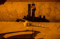 """Street art enthusiasts flock to the Tribeca neighborhood of New York on Tuesday, October 15, 2013 to see the fifteenth installment of Banksy's graffiti art, """"Tribecca"""". The elusive street artist is creating works around the city each day during the month of October and this installment shows a silhouette of the World Trade Center with a flower attached.  (© Richard B. Levine)"""