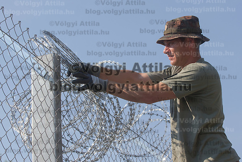 Army soldiers and civilian workers install razor wire to the fence being built on the border between Hungary and Serbia near Asotthalom (about 190 km South of capital city Budapest), Hungary on August 30, 2015. ATTILA VOLGYI