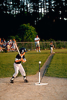 A player at bat during a youth recreational tee ball game.