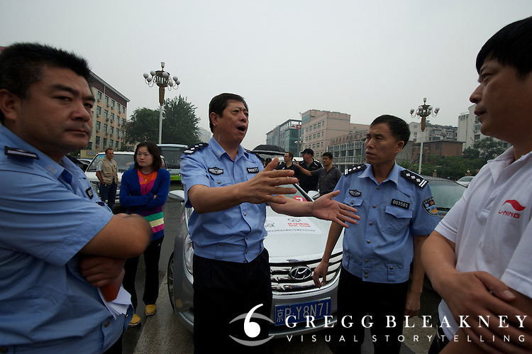 Policemen debate the security details of Stage 2 at the finish line in Mentougou - Stage 2, 133.5km from the Bird's Nest in Beijing to Mentougou via North Gate of Summer Palace.  2011 Tour of Beijing Scouting Photos