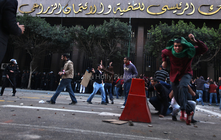 Protesters take cover from police throwing rocks in downtown Cairo, Egypt, Jan. 25, 2011. The day was an official holiday in honor of the achievements of police, but thousands of demonstrators came out to protest corruption, unemployment and police torture.
